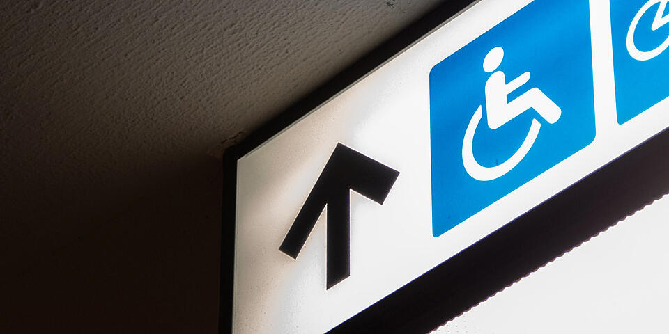 Wayfinding signage up arrow and wheelchair accessible symbol