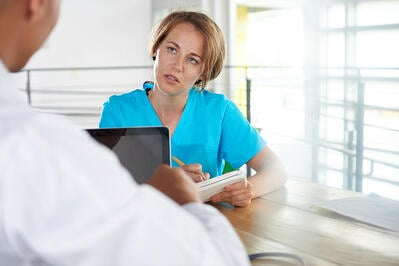 Team of doctor and nurse discussing a patient diagnosis sitting at the desk in bright modern office