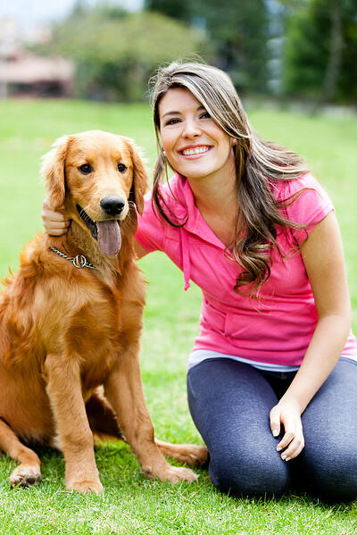 Young woman smiling with a dog at the park