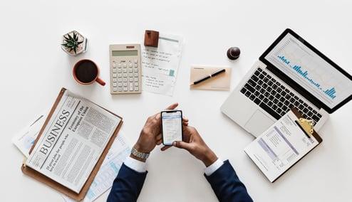 Mann med telefon i hånden og en avis og MacBook ved siden av seg