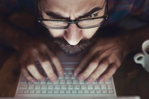 Illustrasjonsbilde tatt i fugleperspektiv. Mann som lener seg over tastatur og skriver ivrig.