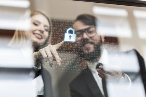 Illustrasjonsbilde. En dame og en mann stående bak en nesten gjennomsiktig skjerm. Skjermen har en rekke tall på seg og en hengelås.