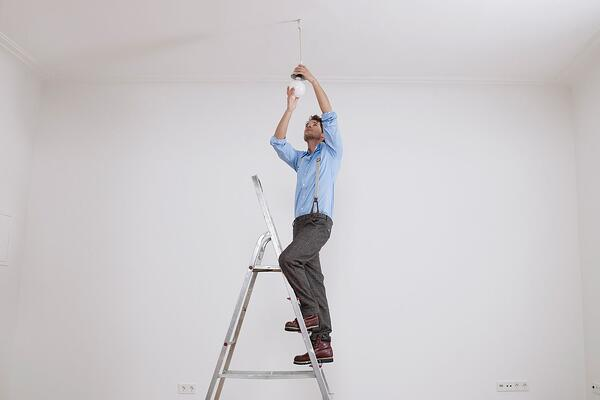 man-climbing-ladder-fixing-light