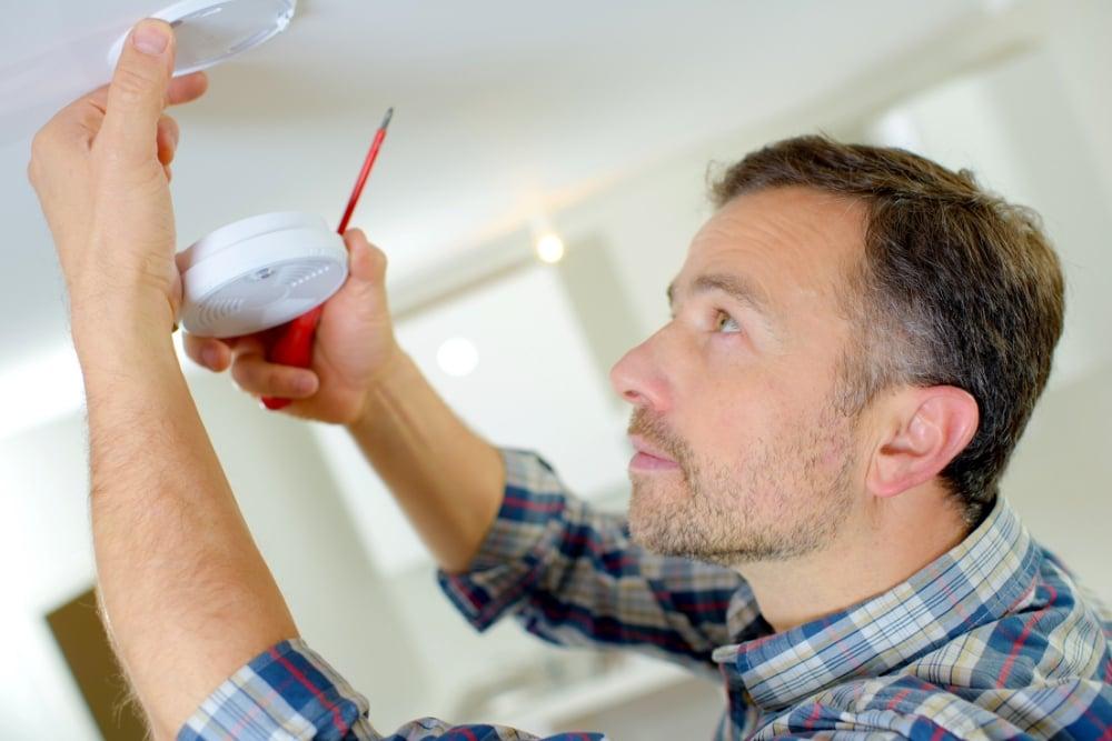 man-installing-smoke-detector-in-ceiling