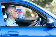 Retired elder man driving a blue car