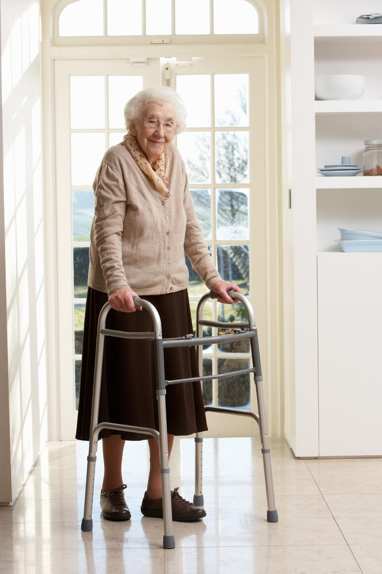 elderly-senior-woman-using-walking-frame-P9WQQ69