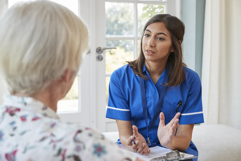 senior-woman-talking-to-young-care-nurse-on-home-P3MELDH