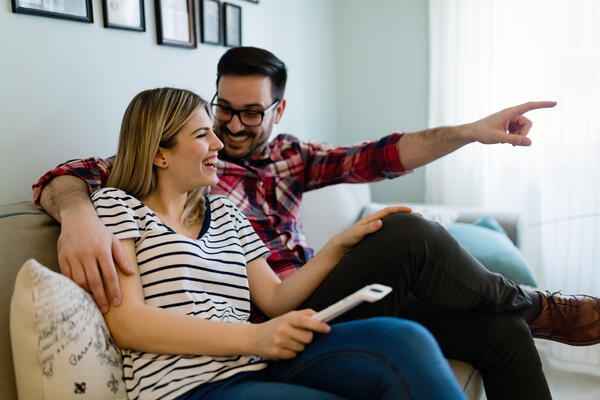 happy-couple-watching-tv-in-their-house-85WJ3PT
