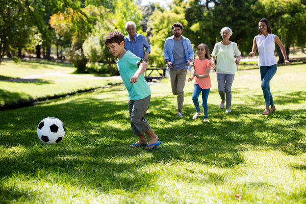 multi-generation-family-playing-football-in-park-M8C4DSW