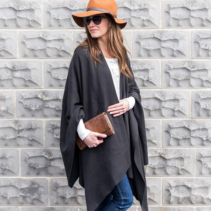 Lady in a tan hat and sunglasses wearing a dark grey organic cotton wrap carrying a tan clutch purse.