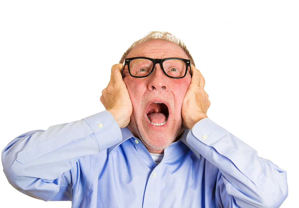 Closeup portrait, angry senior man, nerd black glasses, covering ears, looking up, to say, stop making that loud noise its giving me a headache, isolated white background. Negative human emotion