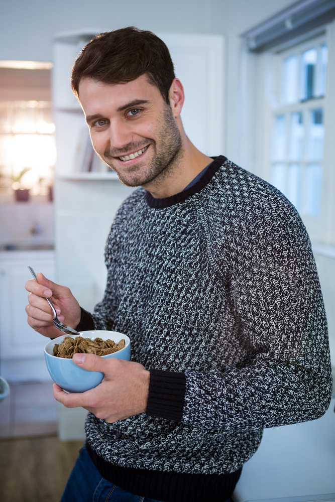 Portrait of man having cereal for breakfast in kitchen at home