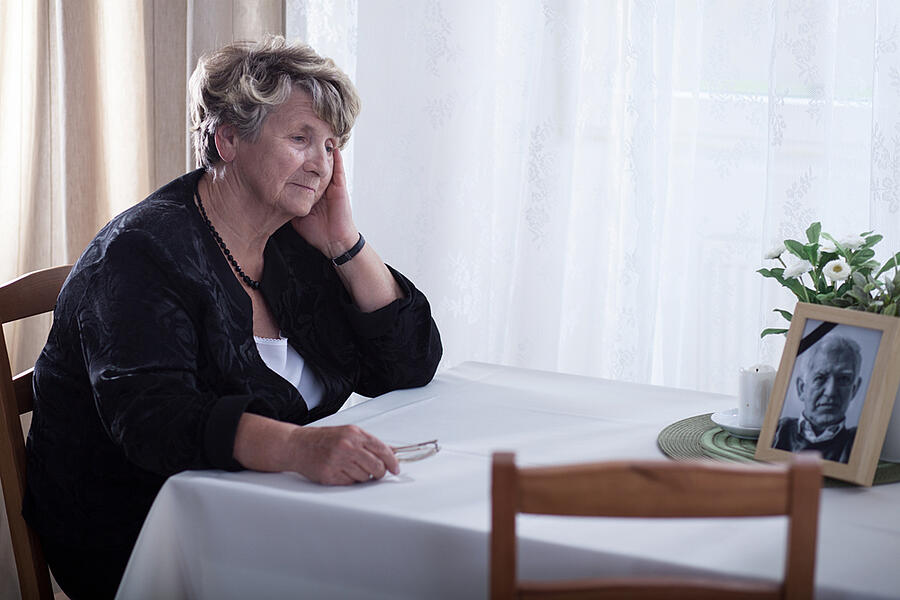 Senior woman looking at dead husbands picture