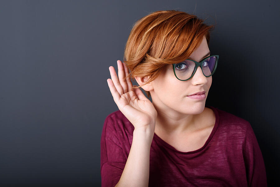 Young woman with a hearing disorder or hearing loss cupping her hand behind her ear with her head turned aside to try and amplify and channel the available sound to her ear drum-1