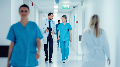 Doctors and nurses walking down hospital hallway leveraging continuous intelligence for real-time patient outcomes