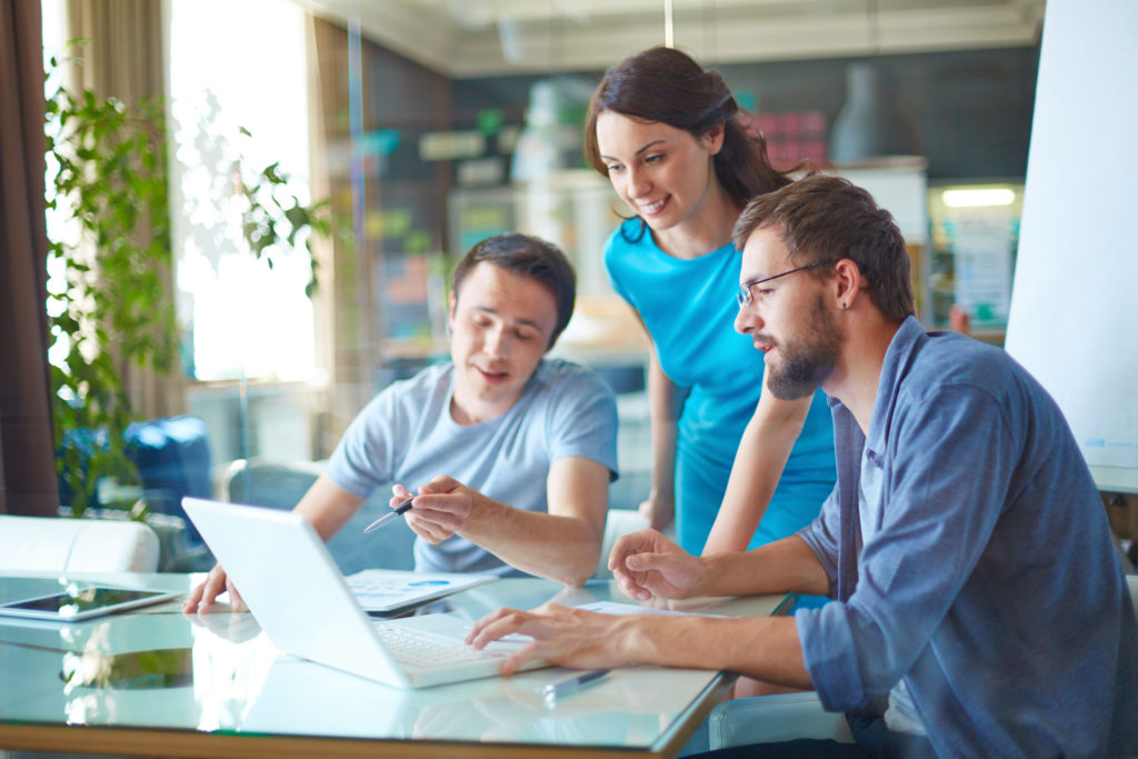 Group of three successful business partners in casual discussing sales at meeting in office