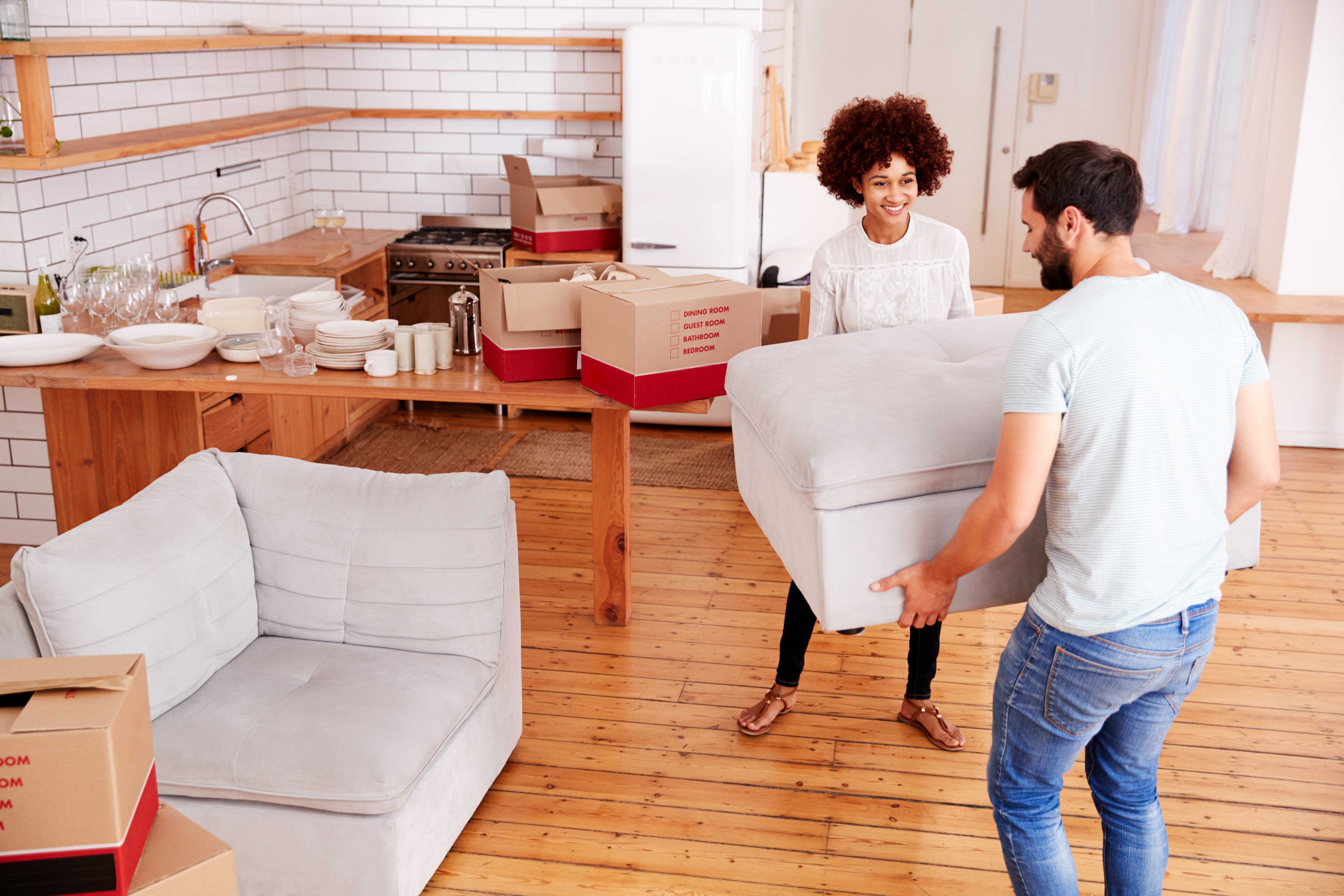 couple moving furniture into a new house