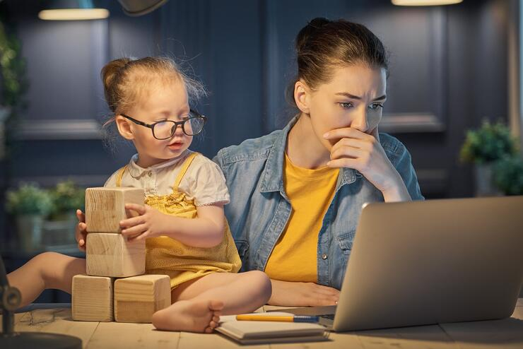 Women working at home with toddler playing blocks