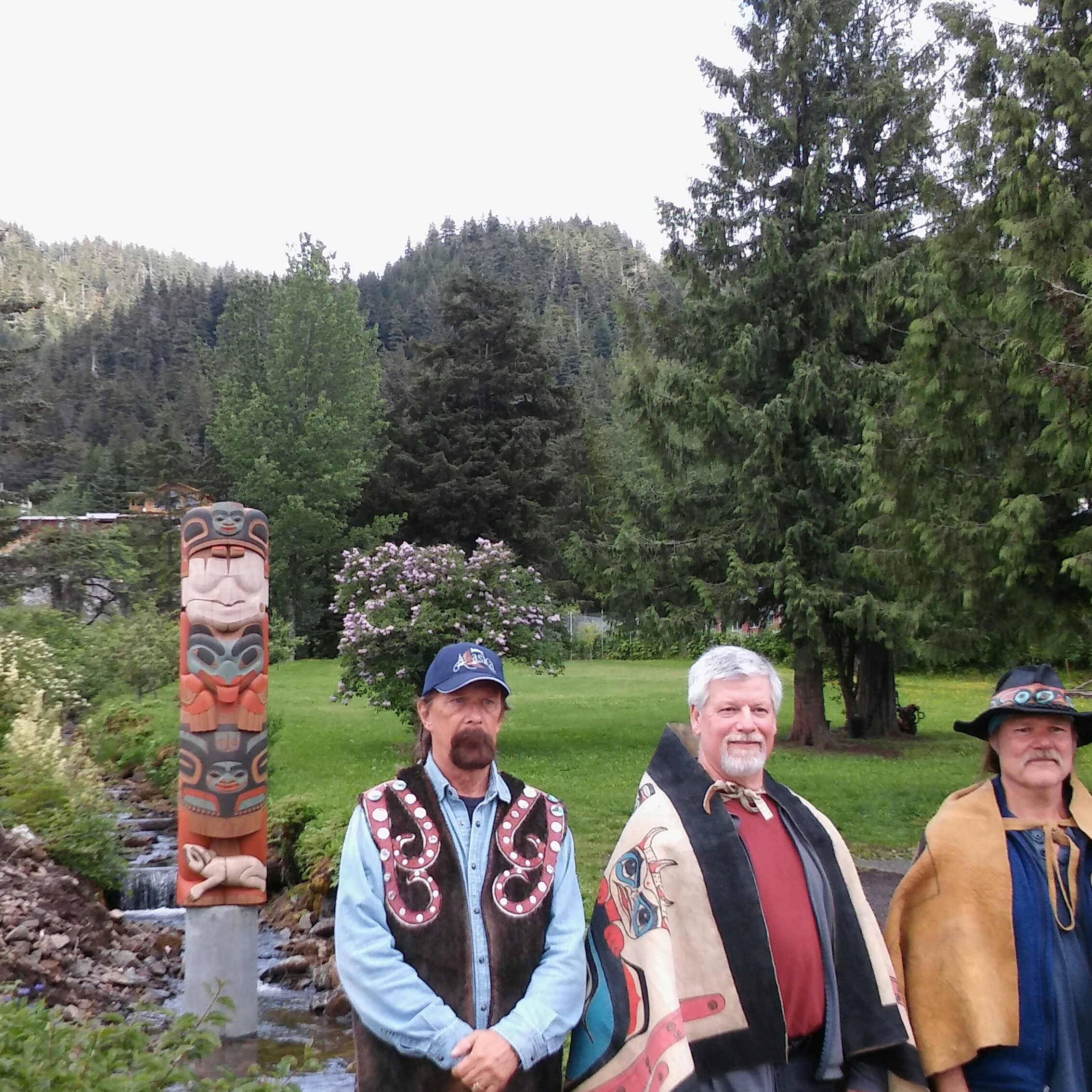 Totem_Pole_with_three_carvers_in_Hoonah.jpg