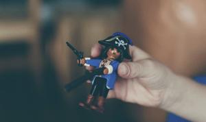 Main qui tient un Playmobil pirate