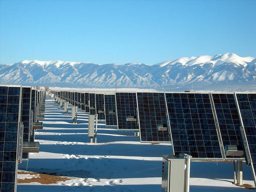 Solar Panels in ice field with snowy mountains