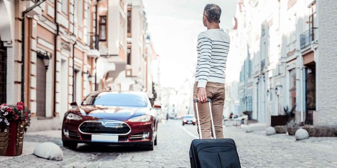 Gast mit Koffer vor eAuto