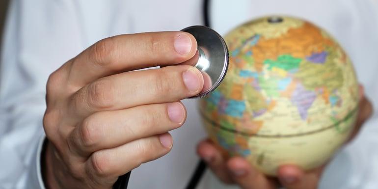 Medico sosteniendo globo terraqueo y estetoscopio