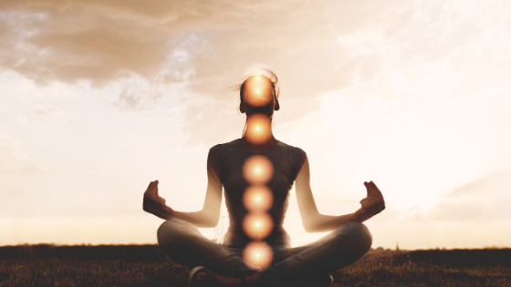 person meditating with activated chakras at peace
