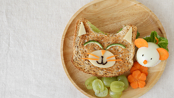 sandwich cut into a cat face with fruits and veggies