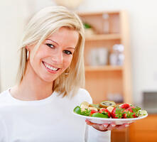 Woman holding plate of fresh fruit and smiling