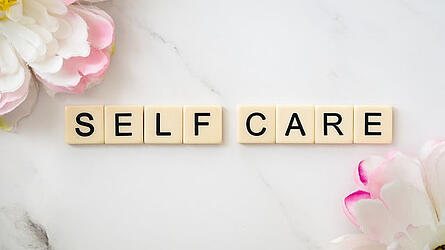 Self Care spelled out with letters pink flowers