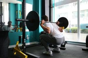 man weight training doing squats