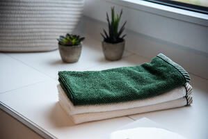 clean towels folded on a clean counter with plants in background