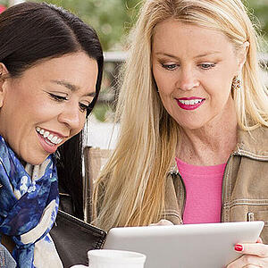 Photo of two women reading a tablet - Helpful SmartSimple features