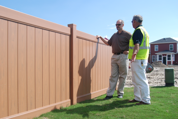 A Hurricane Fence Company project manager meets with a home owner to put finishing touches on a new wood colored vinyl fence enclosure in Virginia Beach Virginia.