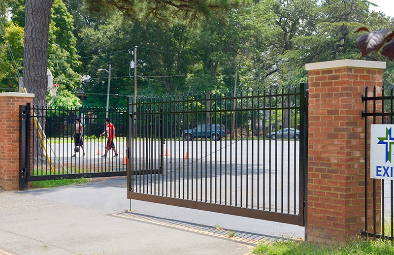 The manual gate enterance to All Saints Catholic School on Noble Avenue in Richmond's Northside updates is surrounded with 8 ft. Industrial Steel spear picket fencing.