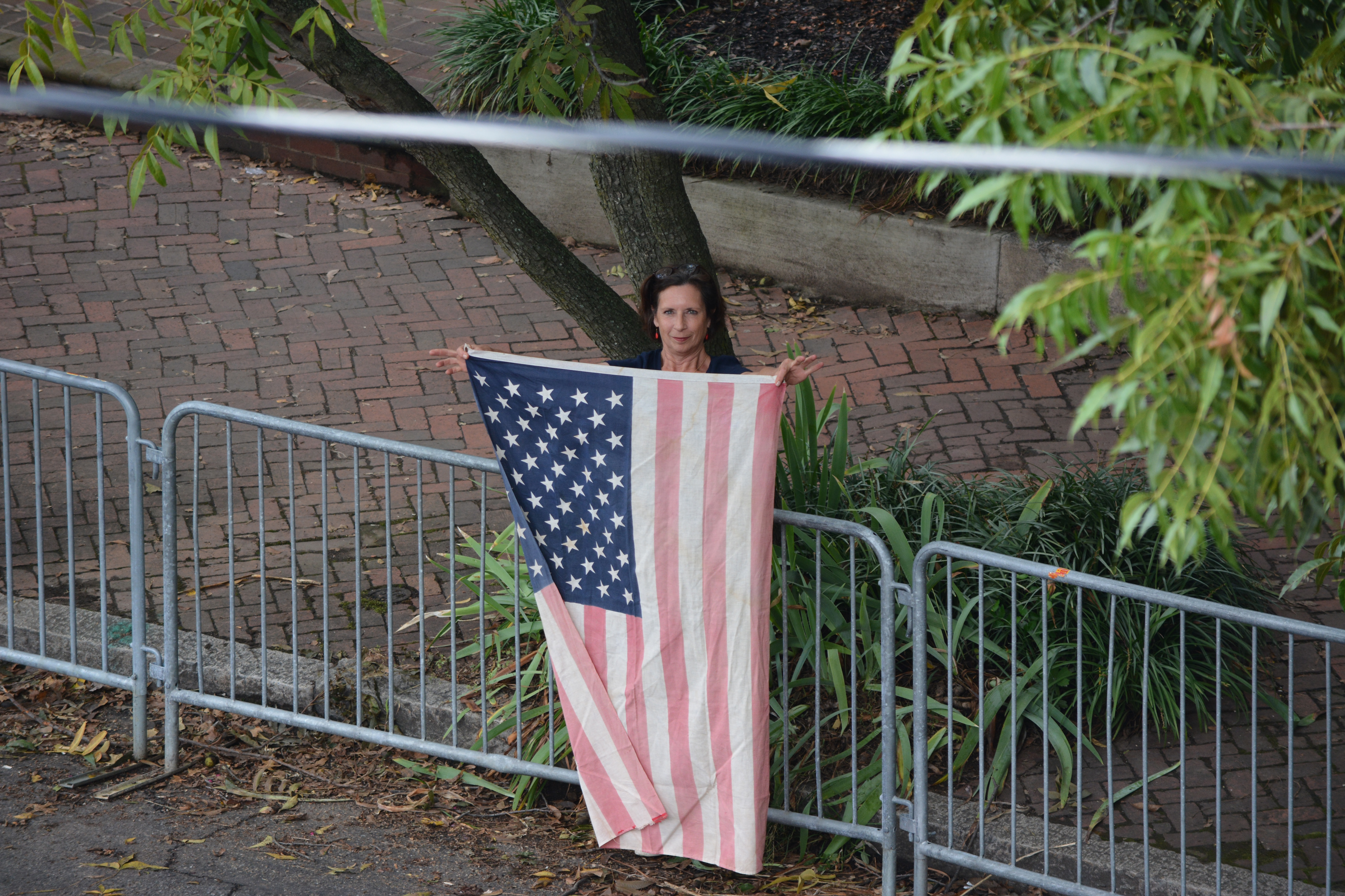 A long time Libby Hill Resident holds up her grandmother's american flag accross a Richmond 2015 barricade