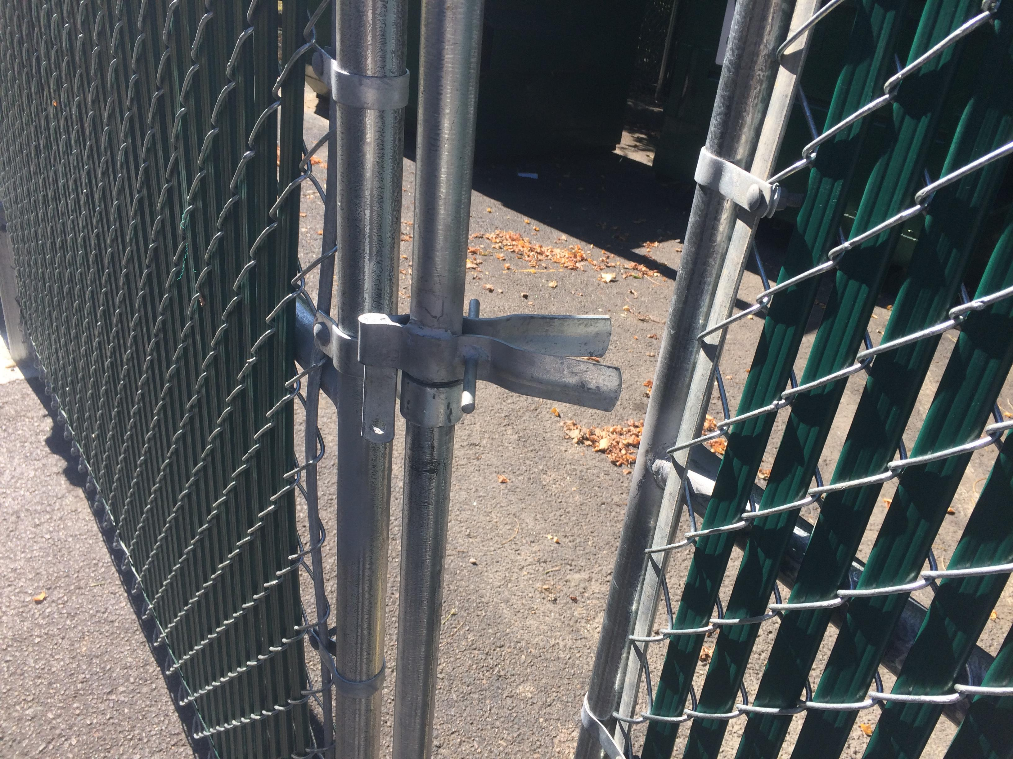 Dumpster enclosure uses chain link fencing and green slats to hide commercial trash cans in Richmond, VA