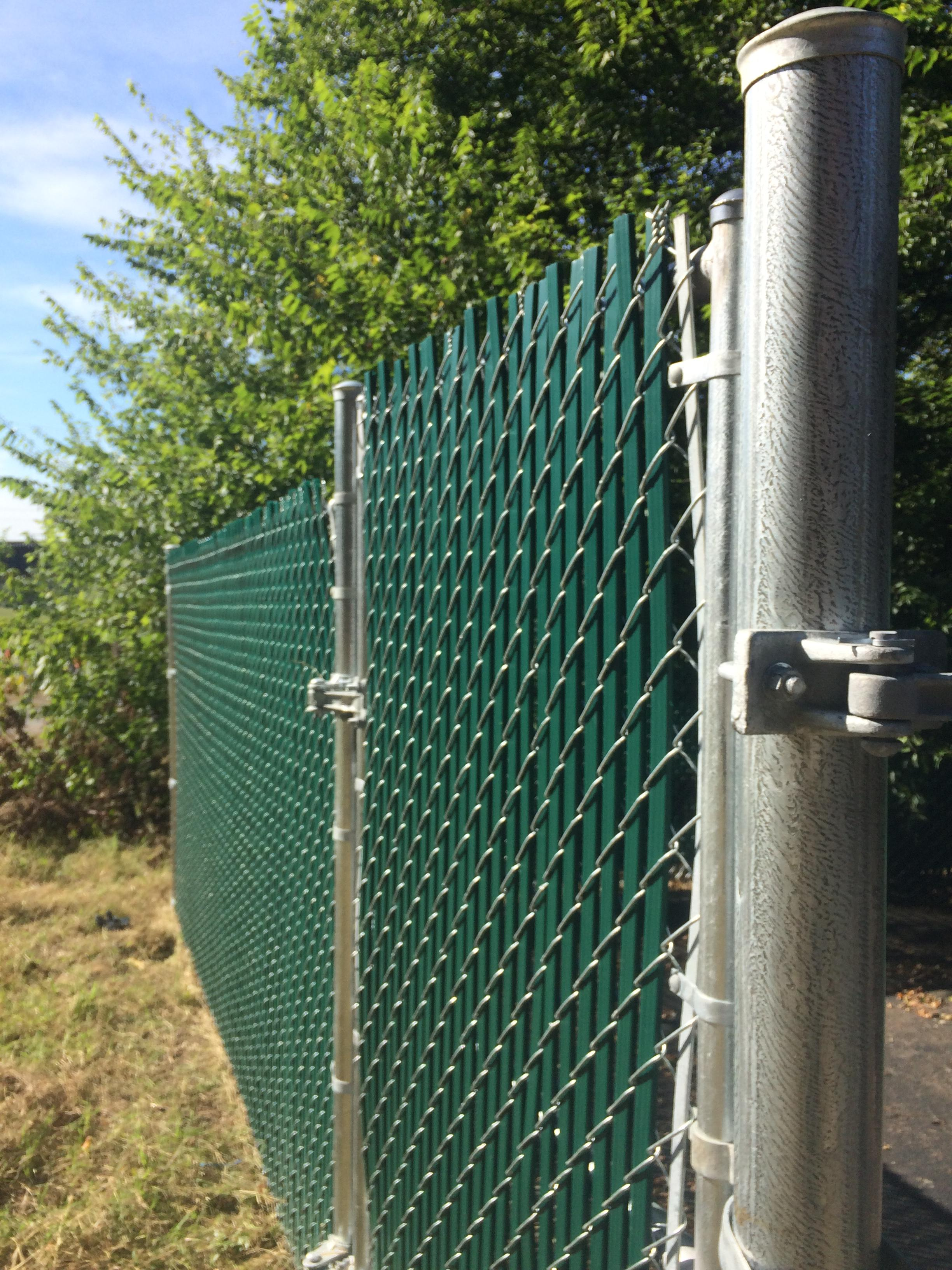 Double panel chain link fence with green privacy slats hides a dumpster at River Lofts in Richmond, VA