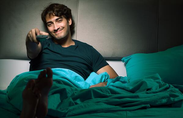 man nesting on couch watching tv