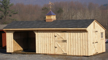 A large unpainted horse shelter built from one of our extended loafing shed kits