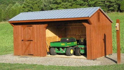 A brown loafing shed built from one of our three-sided shed kits houses a green lawnmower