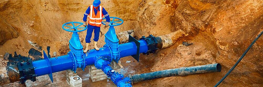 Construction working standing on pipe