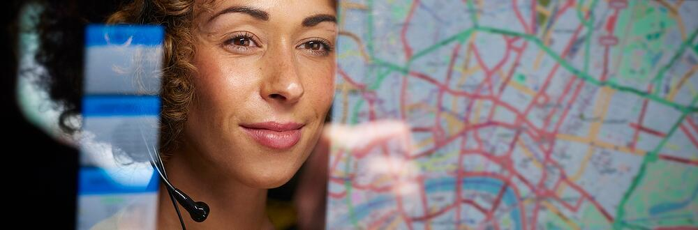 A female with a headset looking at a map and with IoT she has the ability to track assets in real-time.