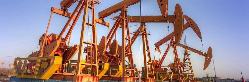 Four, large oil rigs in motion on an oil field.