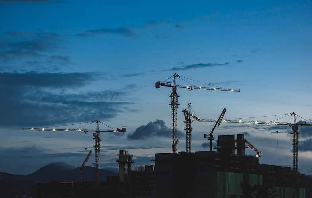 Four tower cranes at dusk as the job site keeps functioning. With equipment monitoring you can keep your job site up and running.