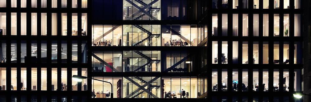A view of a busy office building with several floors of people, conference rooms, and open space environments.