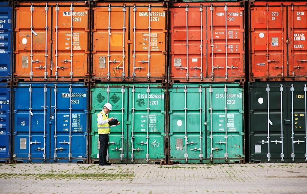 Colorful shipping containers being evaluated by a worker.
