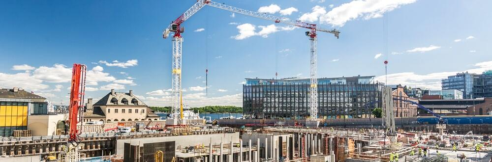 A comprehensive view of an active, metropolitan construction site with two tower cranes.