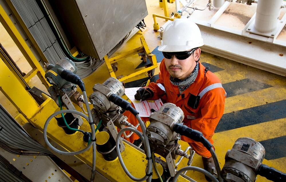 A worker in a hard hat is abstracting information from a machine.